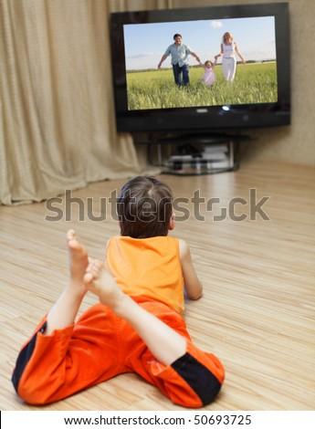Child watching TV, laying on floor - stock photo