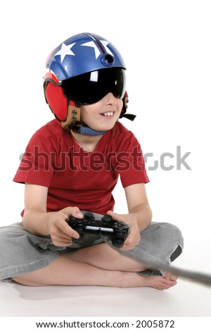 Child wearing a helicopter pilot helmet with visor happily plays a flight simulator computer game. - stock photo