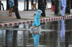 child wearing blue raincoat walking on flood