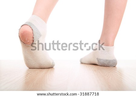 Child wearing dirty socks with holes in the heel