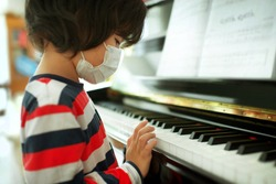 Child wearing face mask playing piano at home.Fingers on keys.Boy having music lesson.Young male musical homeschooling.String instrument.