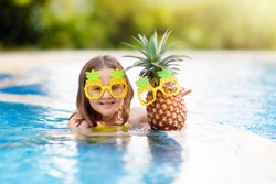 Child wearing funny sunglasses with pineapple in swimming pool. Kids swim in tropical resort. Family summer vacation on exotic island. Fruit for children. Little girl with juice drink on beach holiday