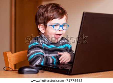 Child wearing glasses using a computer with his tongue out