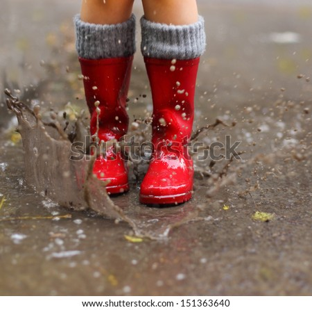 Child wearing red rain boots jumping into a puddle. Close up - stock photo