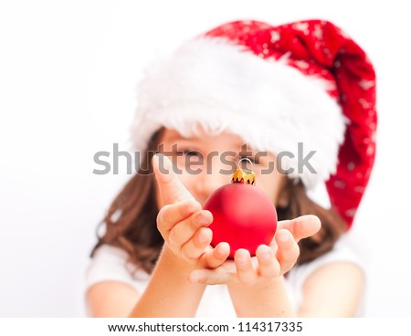 Child wearing santa claus  hat with a christmas ball