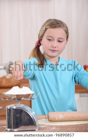Child weighing flour on a scale