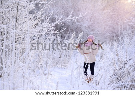 Child winter outdoors. Lots of snow and frost. White tree branches. A girl stands in a frosty forest.