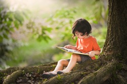 Child with a book. Kids read in park under tree. Cute little Asian boy sitting down in elementary school. Early education for toddler and baby. Summer vacation homework. Preschool student outdoor.