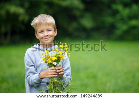 Child with a bouquet of wild flowers - stock photo