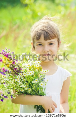 Child with a bouquet of wildflowers. Selective focus. nature. #1397165906