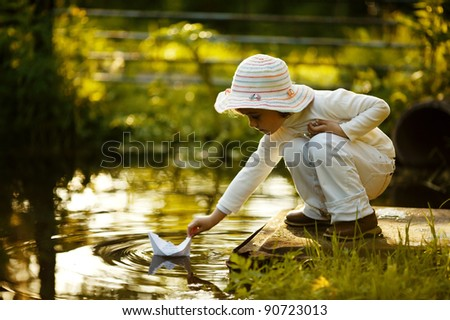 child with a paper boat
