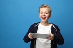 Child with a tablet. Smiling boy with a tablet. Portrait of a child on a colored blue background.