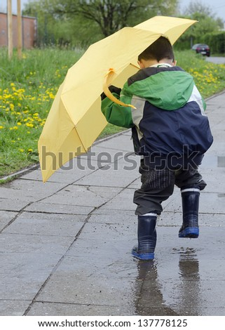 Child with a yellow umbrella jumping into a puddle after the rain.