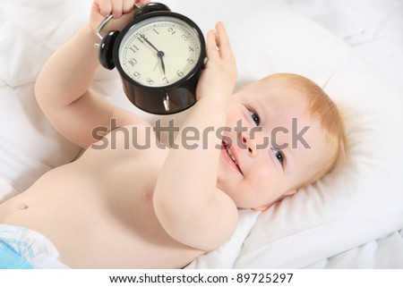 child with an alarm clock lying on the bed, and wishes everyone a good morning