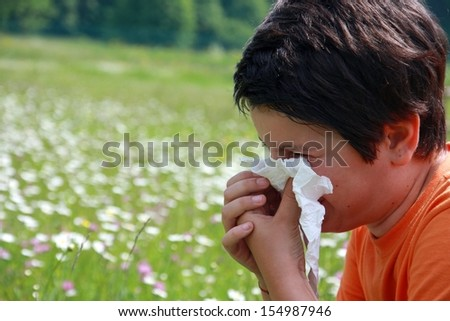 child with an allergy to pollen while you blow your nose with a white handkerchief