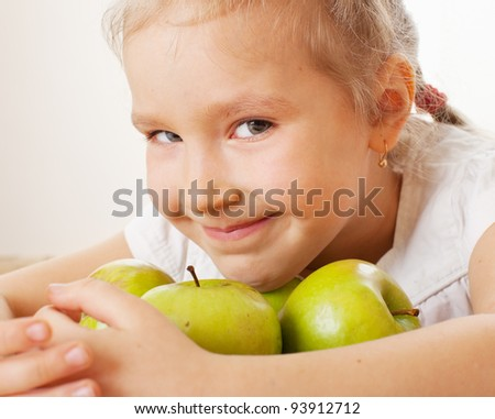 Child with apples. Little girl at home in the kitchen eating fruit - stock photo