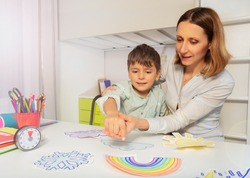 Child with autism spectrum disorder learn weather using cards, teacher hold hands and point to correct one