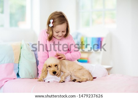 Child with baby dog. Kids play with puppy. Little girl and American cocker spaniel on bed. Pets at home. Animal care. #1479237626