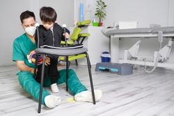 Child with cerebral palsy on physiotherapy in a children therapy center. Boy with disability doing exercises with physiotherapists in rehabitation centre. High quality photo.