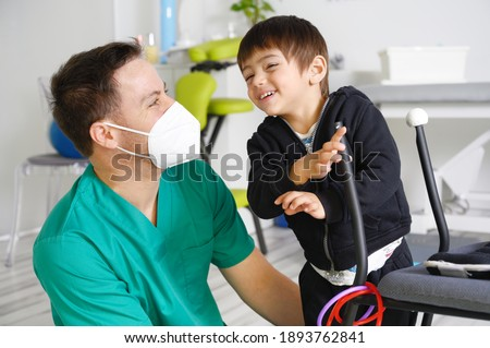 Child with cerebral palsy on physiotherapy in a children therapy center. Boy with disability doing exercises with physiotherapists in rehabitation centre. High quality photo. Stock photo ©