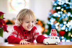 Child with Christmas present. Kid with Xmas gift. Little boy playing with a toy car under Christmas tree. Decorated home for winter holidays. Celebration with children. Kids play.