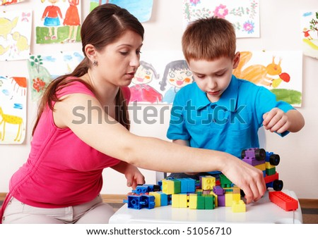 Child with construction  in play room. Preschool.