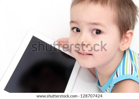 Child with digital tablet look at the camera