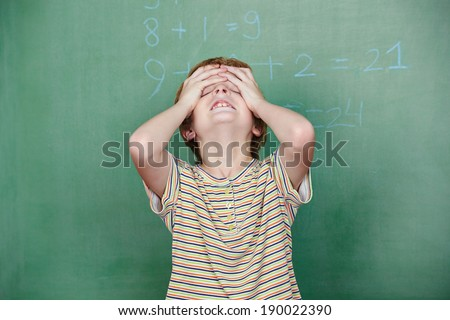 Child with dyscalculia in front of chalkboard in elementary school