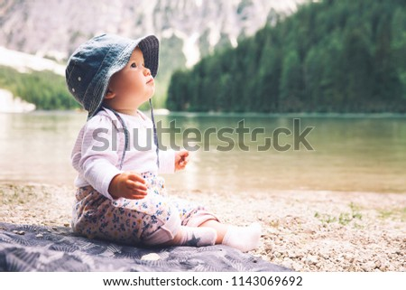Stock Photo Child with family on walk on Braies Lake. Cute baby girl sits on lake shore of Lago di Braies in Dolomites, South Tyrol, Italy, Europe. Beauty of nature image. Little discoverer.