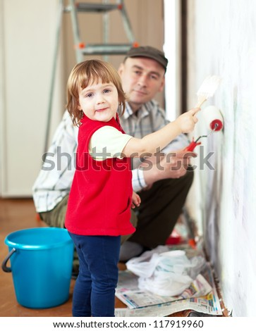 child  with father paints wall  at home