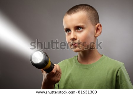 Child with flashlight looking to find answers, studio concept shot