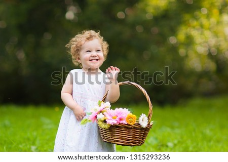 Child with flower basket in sunny park. Little flower girl at wedding outdoor reception. Cute baby with spring flowers. Toddler at kids birthday party. Children play outdoors in summer.