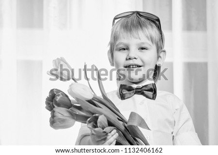 child with flowers for mom. Happy smiling cute little boy gentleman with blonde hair in white shirt and bow tie holding beautiful fresh spring bouquet of colorful tulips for mothers day holiday