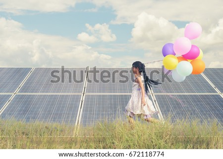 Child with future of alternative energy and sustainable energy. Funny kids holding colorful balloon running in meadow at Solar panel, photovoltaic. Eco-Friendly and Pure energy Concept