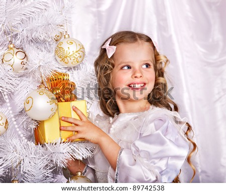 Child with gift box near white Christmas tree. Isolated.
