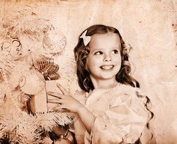Child with gift box near white Christmas tree. Old photo toned sepia.