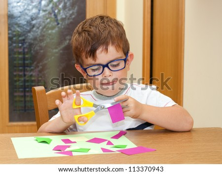 Child with glasses cutting paper with scissors