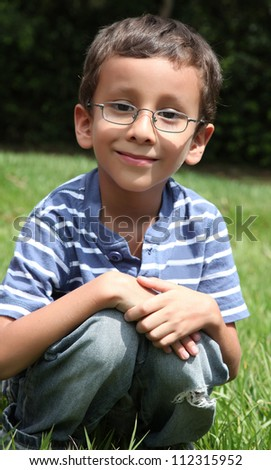 child with glasses looking at the camera with a natural background
