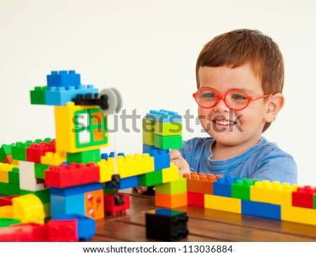 Child with glasses playing with plastic construction