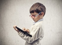 Child with glasses using a laptop computer