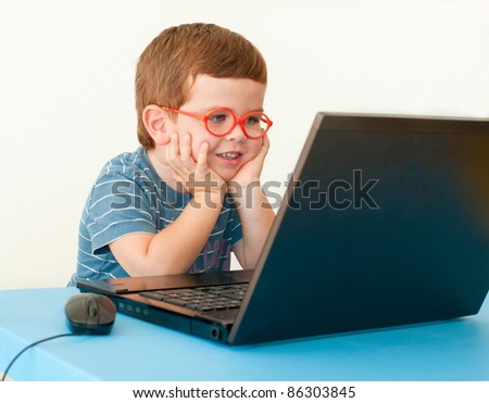 Child with glasses using computer
