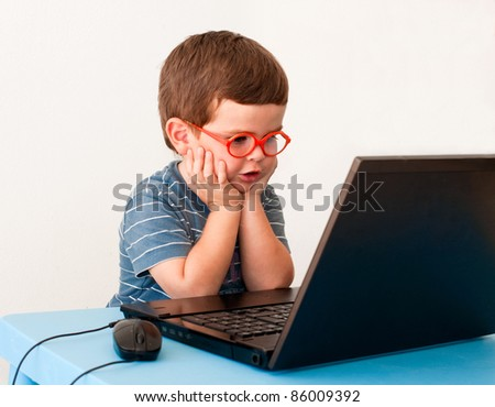 Child with glasses using PC