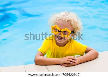 4a551f5af93 Child with goggles in swimming pool. Blond curly little boy learning to swim  in outdoor