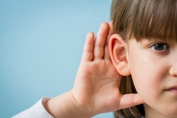 Child with hearing problem on blue background. Hearing loss in childhood, symptoms and treatment concept. Close up, copy space.