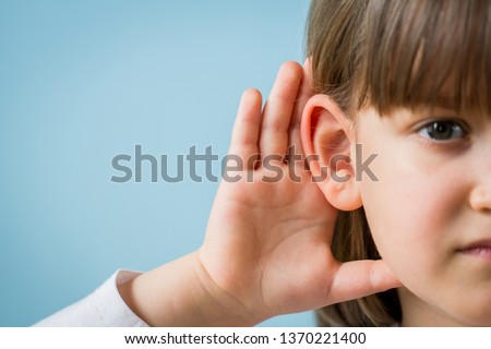 Child with hearing problem on blue background. Hearing loss in childhood, symptoms and treatment concept. Close up, copy space. Foto stock ©