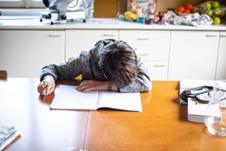 child with his head on the school book desperate cannot do his homework, in the home kitchen