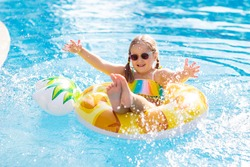 Child with inflatable pineapple toy ring float in swimming pool. Little girl learning to swim and dive in outdoor pool of tropical resort. Swimming with kids. Healthy sport for children. Water fun