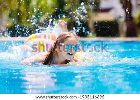 Child with inflatable toy ring float in swimming pool. Little girl learning to swim and dive in outdoor pool of tropical resort. Swimming with kids. Healthy sport activity for children. Water fun.