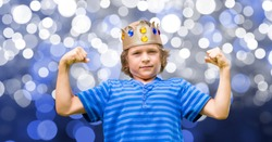 Child with king crown and blue tee shirt and blue background