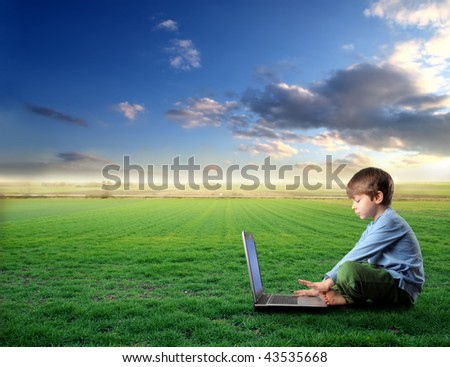 child with laptop in a grass field